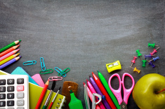 Stock-photo-43463190-school-supplies-on-blackboard-background-1468522917
